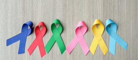 World cancer day (February 4). colorful awareness ribbons; blue, red, green, pink and yellow color on wooden background for supporting people living and illness. Healthcare and medicine concept Stock Photo