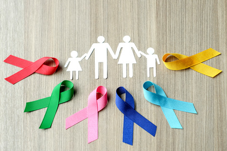 World cancer day (February 4). colorful awareness ribbons; blue, red, green, pink and yellow color on wooden background for supporting people living and illness. Healthcare and medicine concept