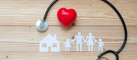 Stethoscope with Red heart shape, Family and House paper on wooden background. Healthcare and Insurance concept