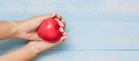 Vue de dessus main tenant forme de coeur rouge sur fond en bois de couleur pastel bleu. soins de santé, don d'organes et assurance ou concepts d'amour et de Saint-Valentin