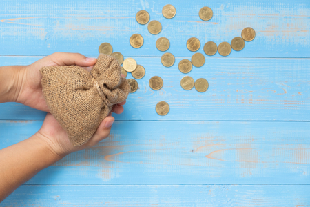 Woman hand holding money sack or bag with coins on blue wooden background. business, finance, retirement and money Saving for investment concept.