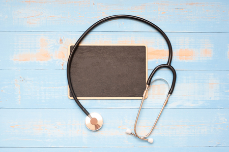 Stethoscope and chalkboard with handwritten words on blue  wooden background. Healthcare and Insurance concept, Top view and Copy space for your text