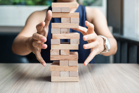 Businesswoman hand cover  wooden block on the tower. Business planning, Risk Management, Solution and strategy Concepts