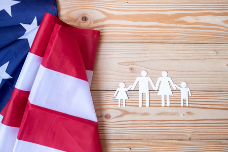 People or Family paper shape with  flag of the United States of America on wooden background. USA holiday of Veterans, Memorial, Independence and Labor Day 免版税图像