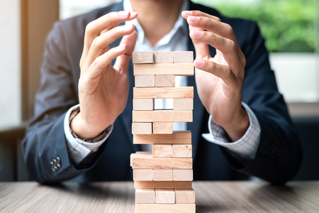 Businessman hand cover wooden block on the tower. Business planning, Risk Management, Solution and strategy