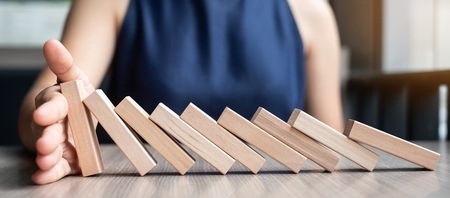 Businesswoman hand Stopping Falling wooden Dominoes. Business, Risk Management, Solution and strategy Фото со стока