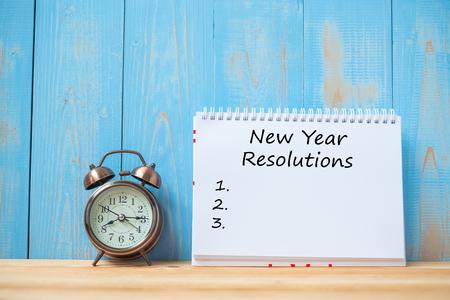 Resoluciones de año nuevo texto en cuaderno y reloj despertador retro en mesa y espacio de copia. Objetivos, misión y concepto de nuevo comienzo