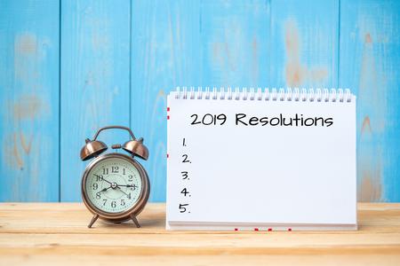 2019 Resoluciones texto en cuaderno y reloj despertador retro en mesa y espacio de copia. Objetivos, misión y concepto de nuevo comienzo