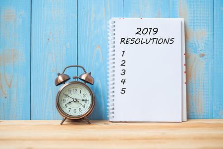 2019 Resoluciones texto en cuaderno y reloj despertador retro en mesa y espacio de copia. Objetivos, misión y concepto de nuevo comienzo Foto de archivo