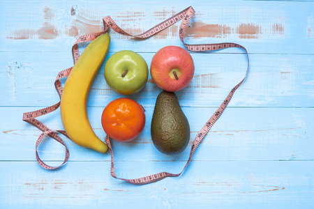 Measuring tape, banana, apple avocado and orange  on blue  wooden background. Healthcare and healthy food concept, Top view and Copy space for your text