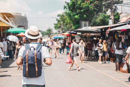 Man traveling backpacker with hat, Asian traveler standing at Chatuchak Weekend Market, landmark and popular for tourist attractions in Bangkok, Thailand. Travel concept Stock Photo