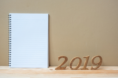 2019 Happy New years with notebook and wooden number on table and copy space. New Start, Resolution, Goals and Mission Concept