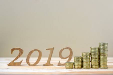 2019 Happy New Year with gold coins stack and wooden number on table. business, investment, retirement planning, finance, Saving and New Year Resolution concepts