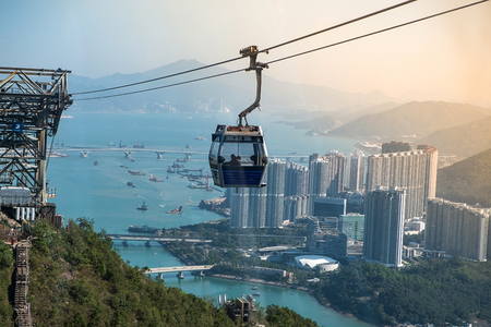 Ngong Ping Cable car with tourists over harbor, mountains and city background, to visit the Tian Tan or the Big Buddha located at Po Lin Monastery in Lantau Island. landmark and popular in Hong Kong