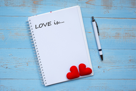 LOVE IS... word on notebook and pen with couple red heart shape decoration on blue wooden table background. Wedding, Romantic and Happy Valentine' s day holiday concept