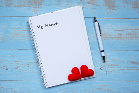 MY HEART word on notebook and pen with couple red heart shape decoration on blue wooden table background. Wedding, Romantic and Happy Valentine' s day holiday concept