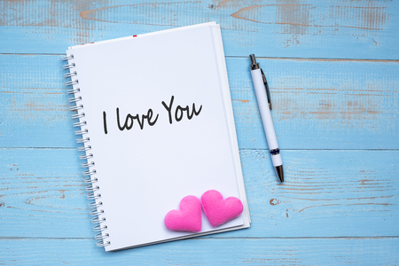 I LOVE YOU word on notebook and pen with couple pink heart shape decoration on blue wooden table background. Wedding, Romantic and Happy Valentine' s day holiday concept