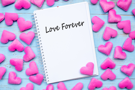 LOVE FOREVER word on notebook with pink heart shape decoration on blue wooden table background. Wedding, Romantic and Happy Valentine' s day holiday concept