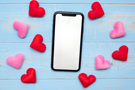 blank touchscreen display of black smart phone with red and pink hearts shape decoration on blue wooden table background. Love, Romantic and Holiday concept