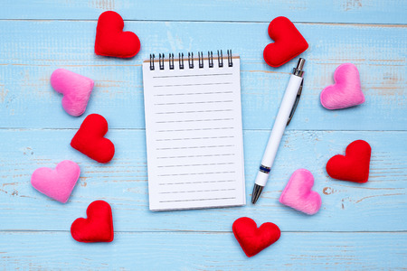 Blank note book and pen with red and pink heart shape decoration on blue wooden table background. Love, Wedding, Romantic and Happy Valentine' s day holiday concept 写真素材