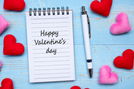 HAPPY VALENTINES DAY word on note book and pen with red and pink heart shape decoration on blue wooden table background. Love, Wedding, Romantic and holiday concept