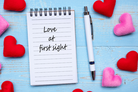LOVE AT FIRST SIGHT word on note book and pen with red and pink heart shape decoration on blue wooden table background. Love, Wedding, Romantic and Valentine' s day concept Фото со стока
