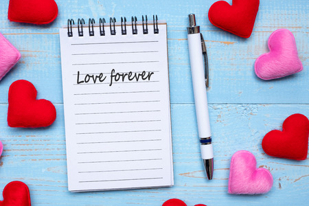 LOVE FOREVER word on note book and pen with red and pink heart shape decoration on blue wooden table background. Love, Wedding, Romantic and Happy Valentine' s day holiday concept