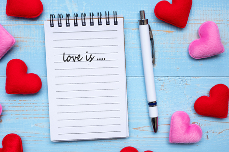 LOVE IS... word on note book and pen with red and pink heart shape decoration on blue wooden table background. Wedding, Romantic and Happy Valentine' s day holiday concept