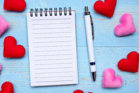 Blank note book and pen with red and pink heart shape decoration on blue wooden table background. Love, Wedding, Romantic and Happy Valentine' s day holiday concept Фото со стока