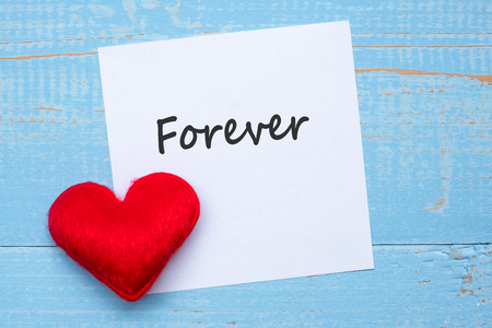 FOREVER word on paper note with red  heart shape decoration on blue wooden table background. Love, Wedding, Romantic and Happy Valentine' s day holiday concept
