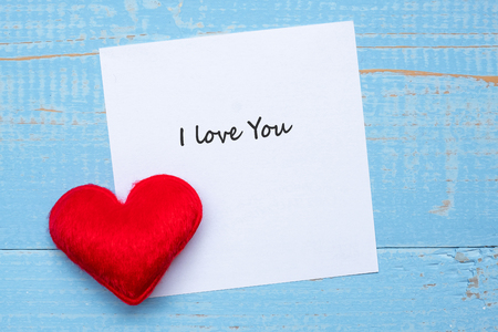 I LOVE YOU word on paper note with red  heart shape decoration on blue wooden table background. Love, Wedding, Romantic and Happy Valentine' s day holiday concept