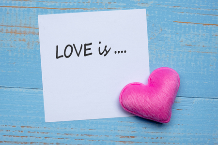 LOVE is... word on paper note with pink heart shape decoration on blue wooden table background. Love, Wedding, Romantic and Happy Valentine' s day holiday concept Stock fotó