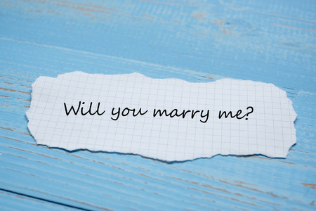 WILL YOU MARRY ME? word on paper note on blue wooden table background. Wedding, Romantic and Happy Valentine' s day holiday concept