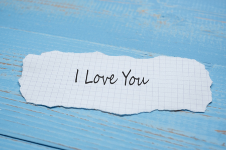 I LOVE YOU word on paper note on blue wooden table background. Wedding, Romantic and Happy Valentine' s day holiday concept