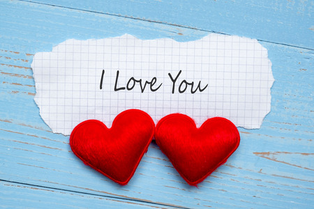 I LOVE YOU word on paper note with couple red heart shape decoration on blue wooden table background. Wedding, Romantic and Happy Valentine' s day holiday concept