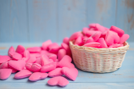 pink heart shape decoration in basket on blue wooden table background. Love, Wedding, Romantic and Happy Valentine' s day holiday concept Banco de Imagens