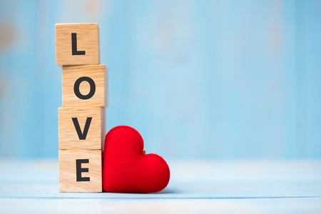 LOVE wooden cubes with red heart shape decoration on blue table background and copy space for text. Love, Romantic and Happy Valentine's day holiday concept Standard-Bild
