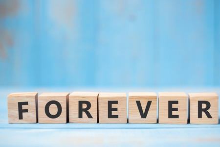 FOREVER wooden cubes on blue table background with copy space for text. Wedding, Romantic and Happy Valentinea€?s day holiday concept