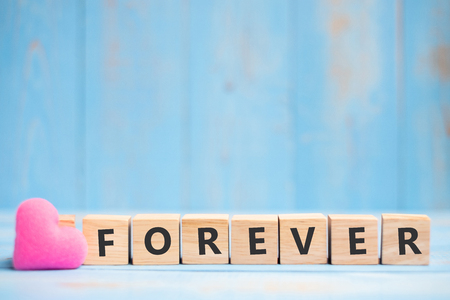 FOREVER wooden cubes with pink heart shape decoration on blue table background and copy space for text. Love, Romantic and Happy Valentine's day holiday concept