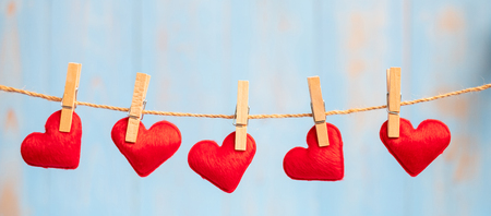 Red heart shape decoration hanging on line with copy space for text on blue wooden background. Love, Wedding, Romantic and Happy Valentinea€? s day holiday concept
