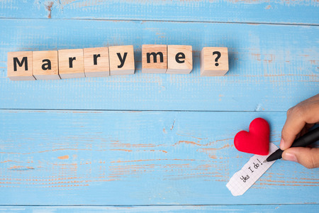 MARRY ME? wooden cubes with red heart shape decoration on blue table background and copy space for text. Love, Romantic and Happy Valentine's day holiday concept Stock Photo