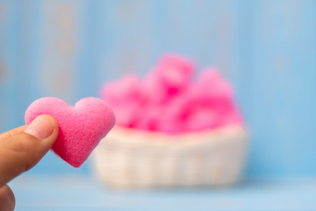 holding pink heart shape decoration in basket on blue wooden table background. Love, Wedding, Romantic and Happy Valentine' s day holiday concept Banco de Imagens