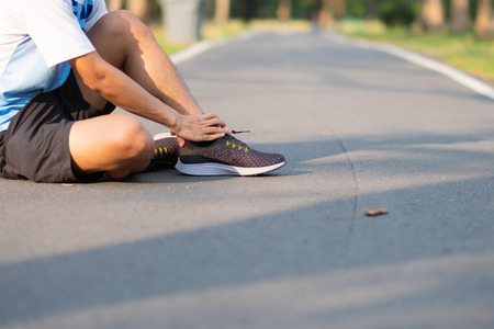 Young fitness man holding his sports leg injury. muscle painful during training. Asian runner having ankle ache and problem after running and exercise outside morning. sport and healthy concepts