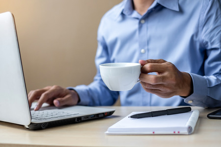 young Businessman using laptop analysis marketing plan and drinking coffee in the morning. Business, Finance and lifestyle concepts