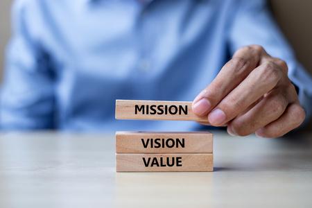 Mano dell'uomo d'affari che tiene i blocchi di costruzione in legno con MISSIONE, VISIONE, VALORE CORE Concepts