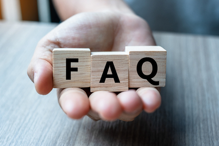 Business man hand holding wooden cube with FAQ text ( frequently asked questions) on table background. Financial, marketing and business concepts