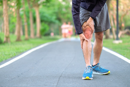 Young fitness man holding his sports leg injury. muscle painful during training. Asian runner having knee ache and problem after running and exercise outside morning. sport and healthy concepts