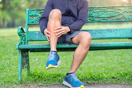 Young fitness man holding his sports leg injury. muscle painful during training. Asian runner having calf ache and problem after running and exercise outside morning. sport and healthy concepts