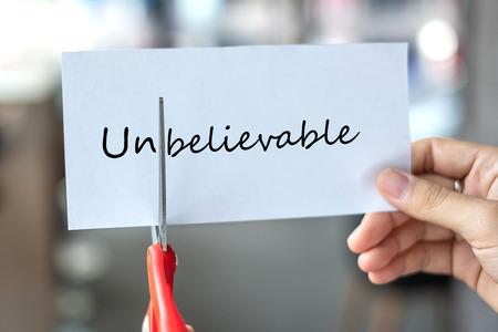 Mano de hombre de negocios sosteniendo tijeras rojas y cortando papel blanco con el texto increíble, cambia la palabra a creíble. desafío, pensamiento positivo y concepto de éxito