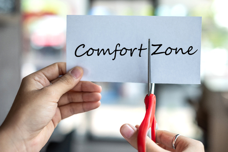 Business man hand holding red scissors and cutting white paper with the text Comfort Zone, change word to Zone. challenge, positive thinking and success concept